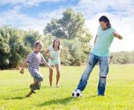 Padres con el niño que juega con el balón de fútbol Imagen de archivo
