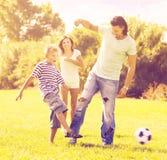 Padres con el niño que juega con el balón de fútbol Fotos de archivo libres de regalías