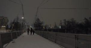 Padres con el niño que lleva a cabo las manos y que camina en ciudad del invierno de la tarde almacen de video