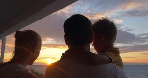 Padres con el niño que mira puesta del sol y que toma el selfie metrajes