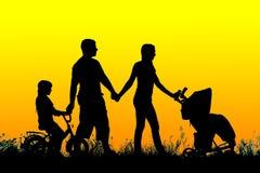Padres con el paseo de los niños en la puesta del sol Imagen de archivo