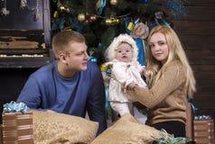 Padres con la hija del bebé en el día de fiesta de la Navidad Fotos de archivo