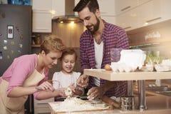 Padres con la hija en la cocina Fotos de archivo libres de regalías
