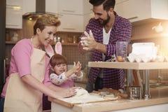 Padres con la hija en la cocina Foto de archivo libre de regalías