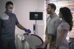 Padres con la hija en la oficina del dentista Foto de archivo