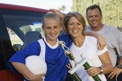 Padres con la hija que sostiene el trofeo del fútbol Foto de archivo libre de regalías