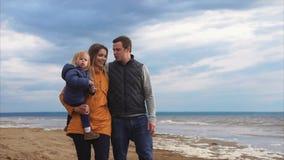Padres con la pequeña hija que camina por el mar en día frío metrajes