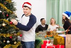Padres con los niños adultos que se preparan para la Navidad Imagen de archivo libre de regalías