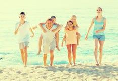 Padres con los niños en hombros en la playa arenosa Fotografía de archivo