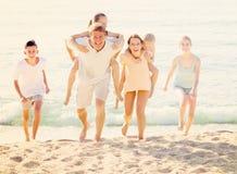 Padres con los niños en hombros en la playa arenosa Imagen de archivo libre de regalías