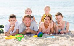 Padres con los niños que mienten en la arena Foto de archivo