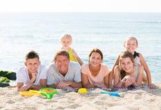 Padres con los niños que mienten en la arena Foto de archivo libre de regalías