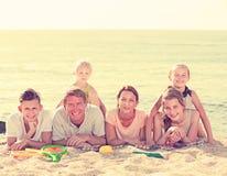 Padres con los niños que mienten en la arena Fotos de archivo