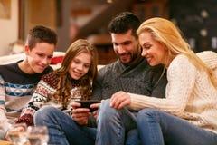 Padres con los niños que miran las fotos en el teléfono celular foto de archivo libre de regalías