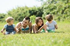 Padres con los niños que ponen en la hierba Fotografía de archivo libre de regalías