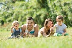 Padres con los niños que ponen en la hierba Imágenes de archivo libres de regalías