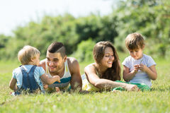 Padres con los niños que ponen en la hierba Foto de archivo