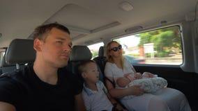 Padres con los niños que viajan en coche almacen de video