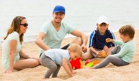 Padres con los niños en la playa Imágenes de archivo libres de regalías