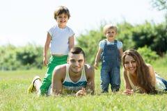 Padres con los niños que ponen en la hierba Imagenes de archivo