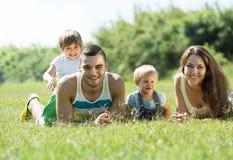 Padres con los niños que ponen en la hierba Foto de archivo libre de regalías