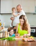 Padres con los pescados dóciles de los niños que cocinan en una cocina casera Foto de archivo