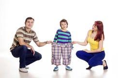 Padres con su hijo en pantalones grandes Foto de archivo
