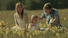 Padres con su hijo feliz que disfruta del día en naturaleza Besan a su hijo de ambos lados almacen de metraje de vídeo