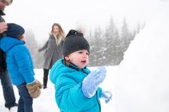 Padres con sus hijos, jugando en la nieve, muñeco de nieve constructivo imagenes de archivo