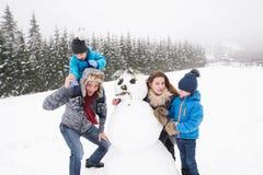 Padres con sus hijos, jugando en la nieve, muñeco de nieve constructivo fotos de archivo libres de regalías