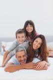 Padres con sus niños que mienten en cama Fotografía de archivo libre de regalías