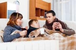 Padres de congelación e hijo adolescente que se calientan cerca del calentador caliente Imagen de archivo
