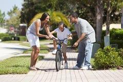 Padres de la familia del afroamericano y bici del montar a caballo del muchacho Imagen de archivo libre de regalías