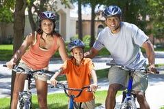 Padres del afroamericano con la bici del montar a caballo del hijo del muchacho Imagen de archivo