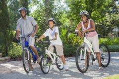 Padres del afroamericano con la bici del montar a caballo del hijo del muchacho fotos de archivo libres de regalías