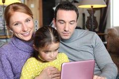 Padres e hija con el ordenador portátil Foto de archivo