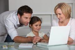Padres e hija en la computadora portátil Foto de archivo libre de regalías