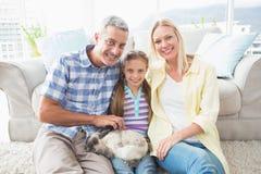 Padres e hija felices con el conejo en sala de estar Imagenes de archivo