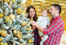 Padres e hija jovenes del niño cerca del árbol de navidad adornado en casa imagen de archivo