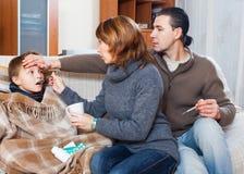 Padres e hijo con el termómetro Imagen de archivo libre de regalías