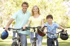 Padres e hijo en paseo del ciclo en parque Foto de archivo