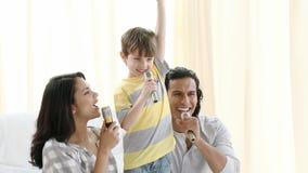 Padres e hijo que cantan en casa almacen de video