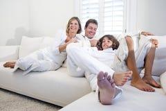 Padres e hijo que se relajan junto en el sofá blanco Foto de archivo libre de regalías