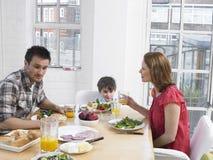 Padres e hijo que tienen comida en la mesa de comedor Foto de archivo