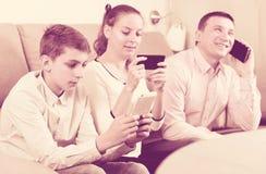 Padres e hijo que usa los teléfonos Foto de archivo