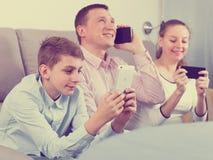 Padres e hijo que usa los teléfonos Foto de archivo libre de regalías