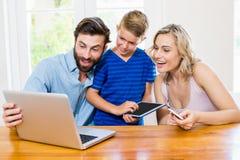 Padres e hijo que usa un ordenador portátil, una tableta y un teléfono Fotografía de archivo