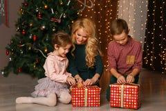 Padres emocionados felices que miran cómo hija que abre Navidad presente Fotografía de archivo libre de regalías