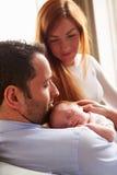 Padres en casa con la hija recién nacida durmiente del bebé Foto de archivo