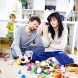 Padres en casa desesperados sobre el lío de juguetes Imagen de archivo